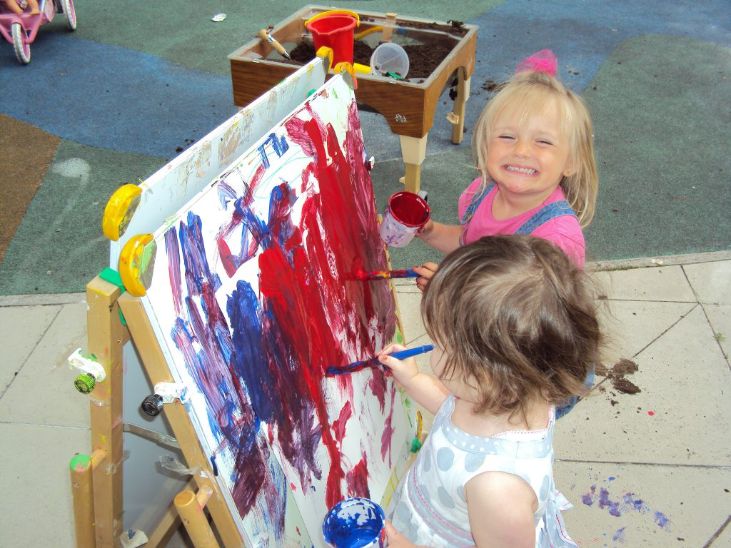 Two little girls painting at the Children's Centre