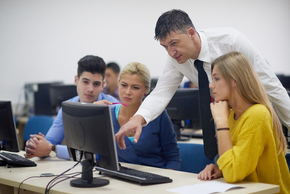 Teacher giving lessons to group of students in a computer lab