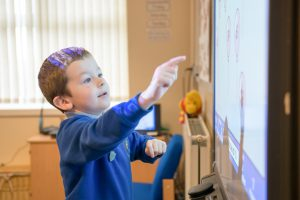 Child pressing on a smart board