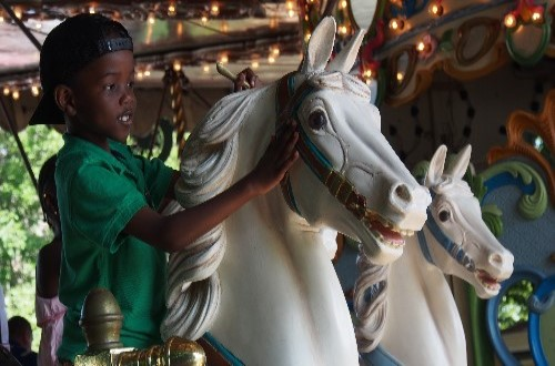 Young boy riding on a carousel at an amusement park