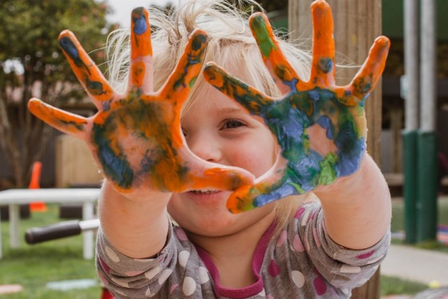 Child with paint on hands doing fingerpainting