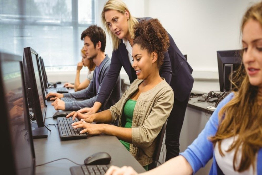 Students sat at computers with teacher looking on