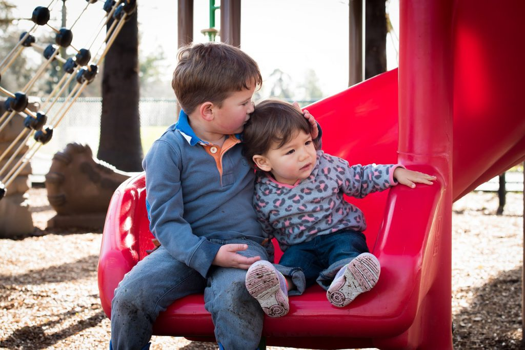 Little boy and toddler on a slide