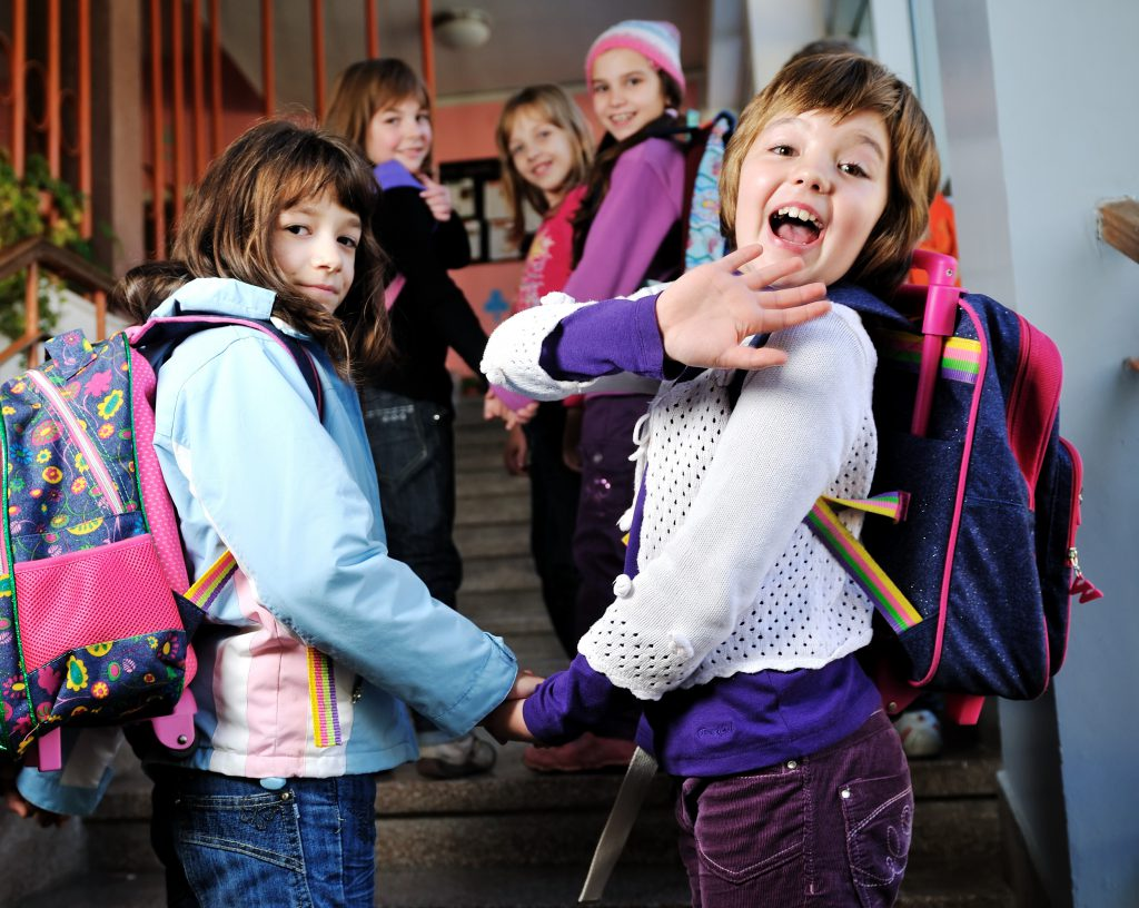 Children waving goodbye as they go into school
