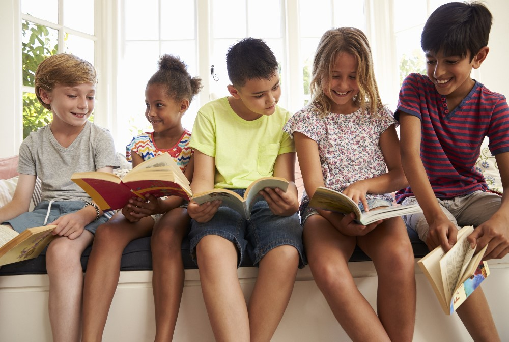 Group of children sitting on a bench reading books