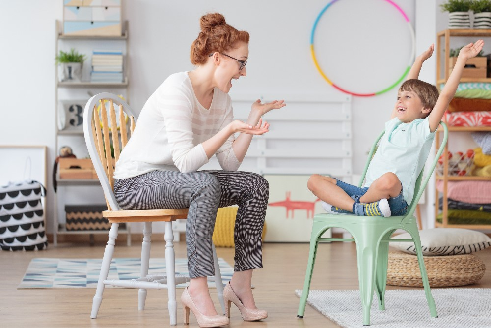 Childminder talking to young boy