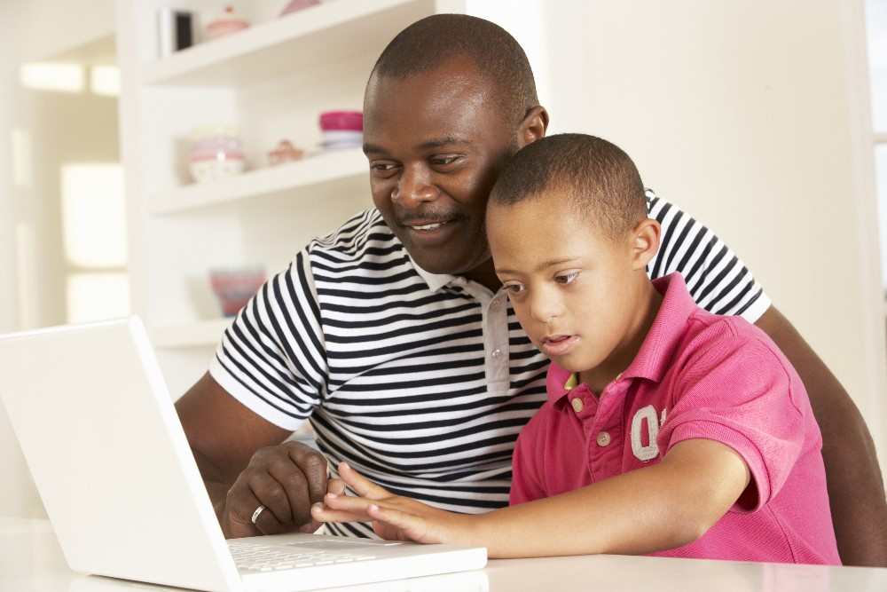 Parent showing child how to use a computer