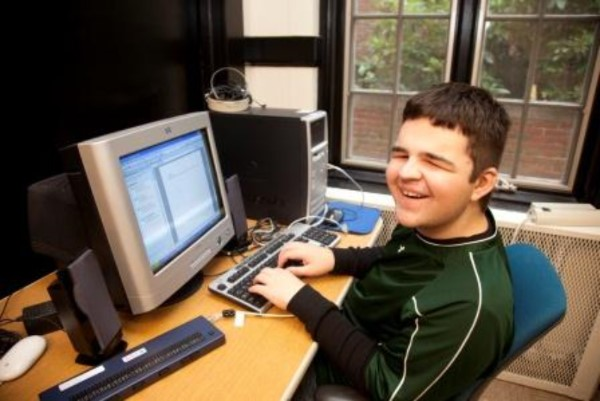 Boy with disability working at computer