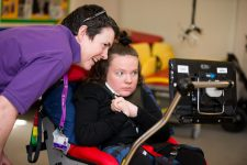 Carer showing girl in wheelchair information on a screen