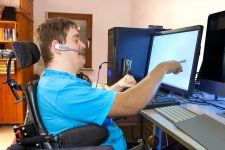 Disabled man in wheelchair working on a computer