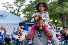 Dad carrying a little girl on his shoulders at an outdoor event