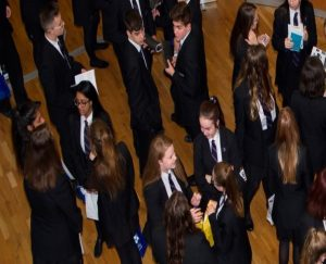 Large group of mixed teenagers in school uniforms having a discussion