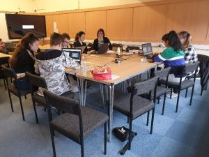 Mixed group of young people learning how to make videos on laptops