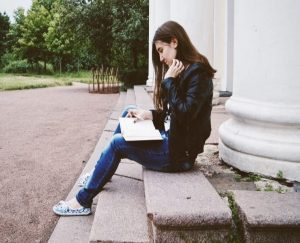 Teenage girl sitting on steps and reading a notebook